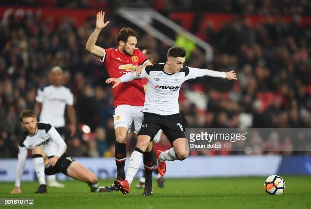 Tom Lawrence of Derby County holds off Daley Blind of Manchester United during the Emirates FA Cup Third Round match between Manchester United and...