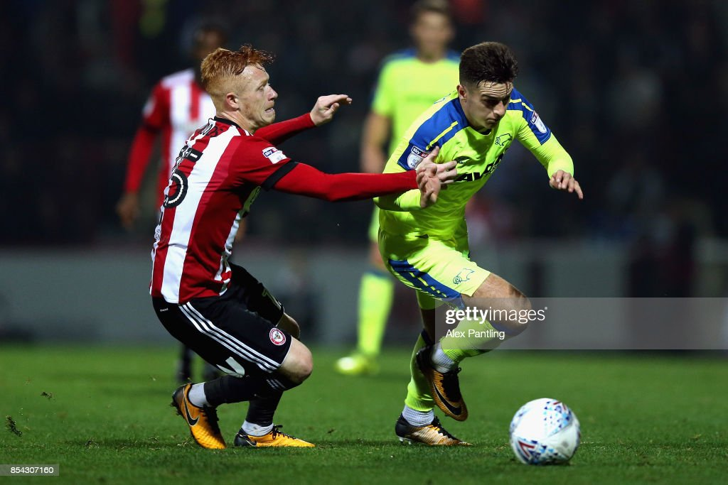 Tom Lawrence of Derby County is pulled back by Ryan Woods of Brentford during the Sky Bet Championship match between Brentford and Derby County at Griffin Park on September 26, 2017 in Brentford, England.