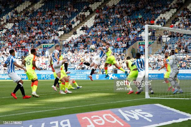 Tom Lees of Huddersfield Town tries to get to a header on from Ollie Turton during the Sky Bet Championship match between Huddersfield Town and...