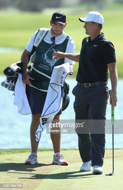 Tom Lewis of England stands with his caddie Jonathan Bell on the 17th hole during the third round of the Portugal Masters at Dom Pedro Victoria Golf...