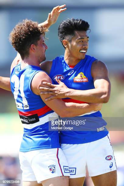 Tom Liberatore and Lin Jong of the Bulldogs celebrates a goal during the JLT Community Series AFL match between Collingwood Magpies and the Western...