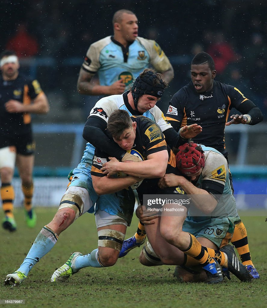 Tom Lindsay of London Wasps is tackled by Tom Wood and Christian Day (r) of Northampton Saints during the Aviva Premiership match between London Wasps and Northampton Saints at Adams Park on March 23, 2013 in High Wycombe, England.