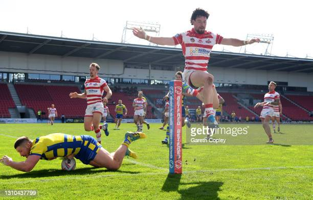 Tom Lineham of Warrington scores a second half try past Blake Wallace of Leigh during the Betfred Super League match between Warrington Wolves and...