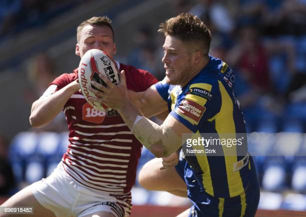 Tom Lineham of Warrington Wolves and of Liam Marshall of Wigan Warriors in action during the Ladbrokes Challenge Cup QuarterFinal match between...