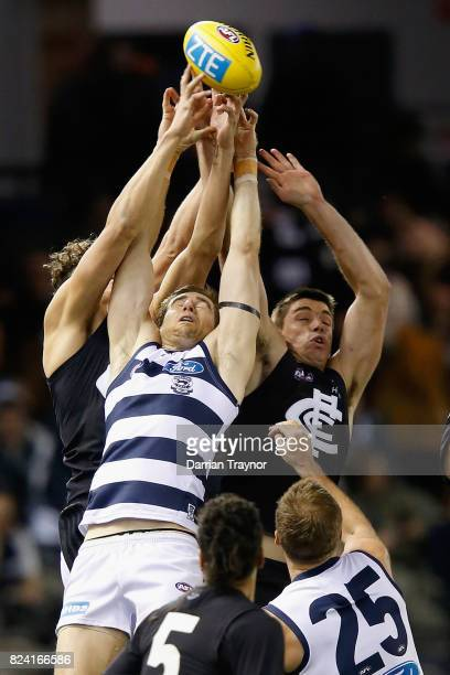 Tom Lonergan of the Cats and Matthew Kreuzer of the Blues compete during the round 19 AFL match between the Carlton Blues and the Geelong Cats at...