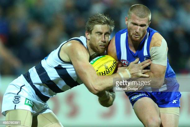 Tom Lonergan of the Cats gets hit in the head by Leigh Adams of the Kangaroos during the round 10 AFL match between the Geelong Cats and the North...