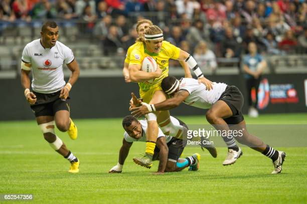 Tom Lucas of Australia runs past team Fiji defenders during day 2 of the 2017 Canada Sevens Rugby Tournament on March 12 2017 in Vancouver British...