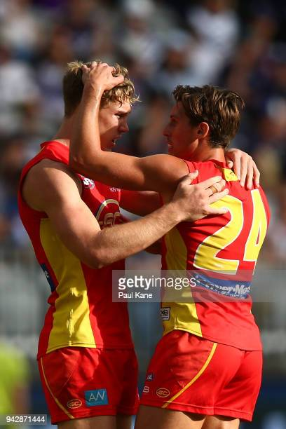 Tom Lynch and David Swallow of the Suns celebrate a goal during the round three AFL match between the Gold Coast Suns and the Fremantle Dockers at...