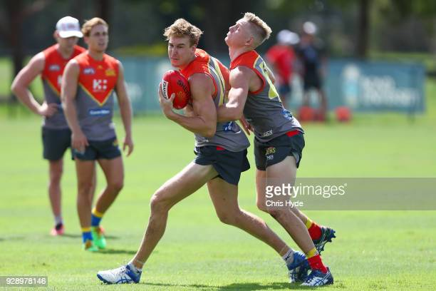 Tom Lynch and Max Spencer compete for the ball during a Gold Coast Suns AFL training session at Bond University AFL Field on March 8 2018 in Gold...