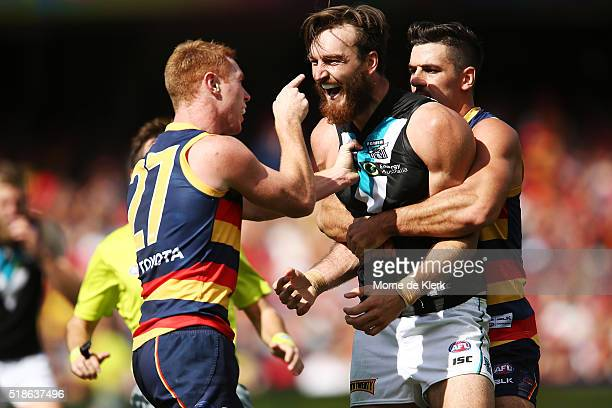 Tom Lynch of the Crows has words with Charlie Dixon of the Power as Taylor Walker holds Dixon during the round two AFL match between the Adelaide...