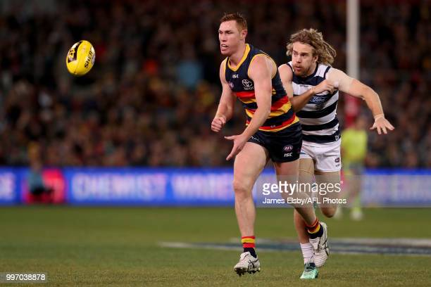 Tom Lynch of the Crows is tackled by Cameron Guthrie of the Cats during the 2018 AFL round 17 match between the Adelaide Crows and the Geelong Cats...
