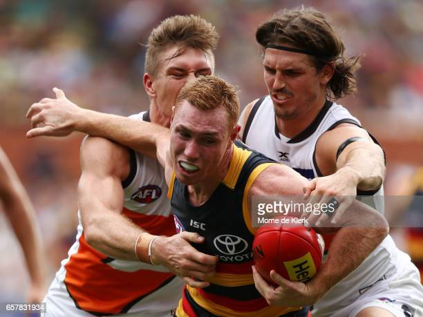 Tom Lynch of the Crows is tackled by Phil Davis of the Giants during the round one AFL match between the Adelaide Crows and the GWS Giants at...