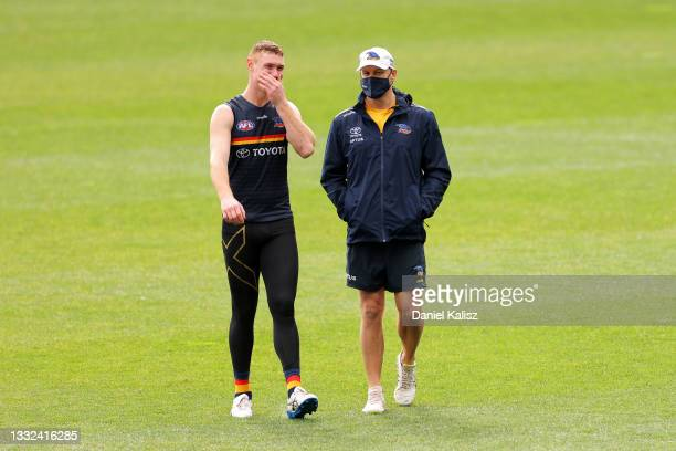 Tom Lynch of the Crows talks with Matthew Nicks, head coach of the Crows during an Adelaide Crows AFL training session at Adelaide Oval on August 05,...