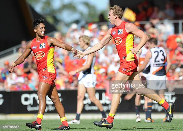 Tom Lynch of the Suns celebrates kicking a goal with Aaron Hall during the round six AFL match between the Gold Coast Suns and the Greater Western...
