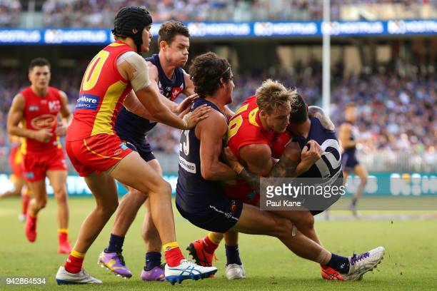 Tom Lynch of the Suns gets tackled by Alex Pearce and Michael Walters of the Dockers during the round three AFL match between the Gold Coast Suns and...
