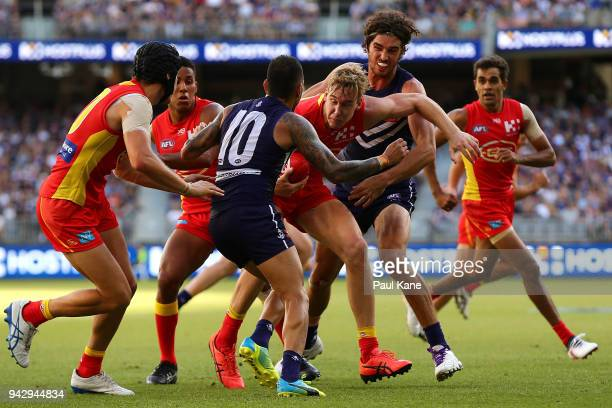 Tom Lynch of the Suns gets tackled by Michael Walters and Alex Pearce of the Dockers during the round three AFL match between the Gold Coast Suns and...