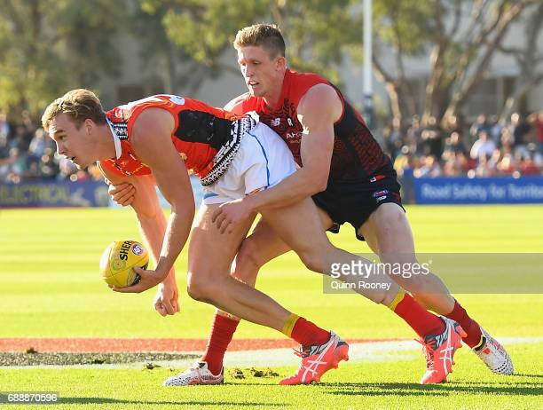 Tom Lynch of the Suns handballs whilst being tackled by Sam Frost of the Demons during the round ten AFL match between the Melbourne Demons and the...