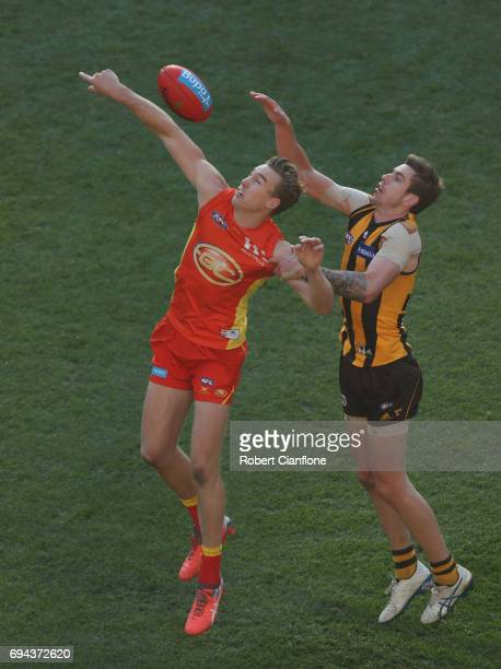 Tom Lynch of the Suns is challenged by Kaiden Brand of the Hawks during the round 12 AFL match between the Hawthorn Hawks and the Gold Coast Suns at...