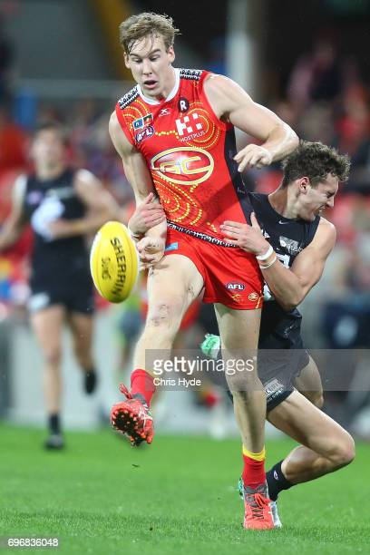 Tom Lynch of the Suns is tackled by Kade Simpson of the Blues during the round 13 AFL match between the Gold Coast Suns and the Carlton Blues at...