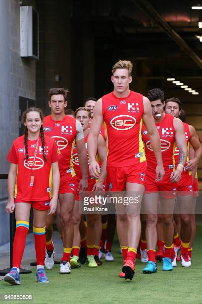 Tom Lynch of the Suns leads his team onto the field during the round three AFL match between the Gold Coast Suns and the Fremantle Dockers at Optus...