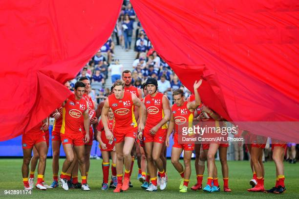Tom Lynch of the Suns leads the team through the banner during the 2018 AFL round 03 match between the Gold Coast Suns and the Fremantle Dockers at...