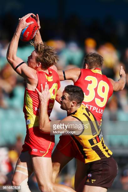 Tom Lynch of the Suns marks the ball against James Frawley of the Hawks during the round 14 AFL match between the Hawthorn Hawks and the Gold Coast...