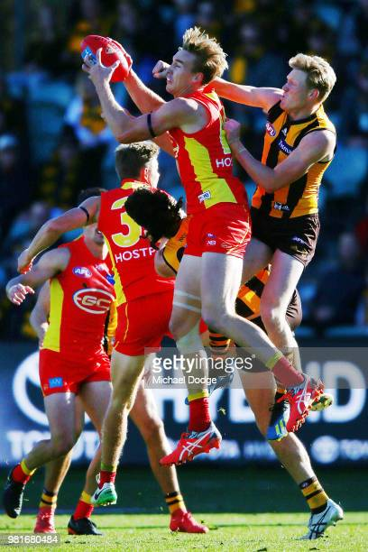 Tom Lynch of the Suns marks the ball against James Sicily of the Hawks during the round 14 AFL match between the Hawthorn Hawks and the Gold Coast...
