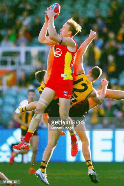 Tom Lynch of the Suns marks the ball against Ricky Henderson and James Frawley of the Hawks during the round 14 AFL match between the Hawthorn Hawks...