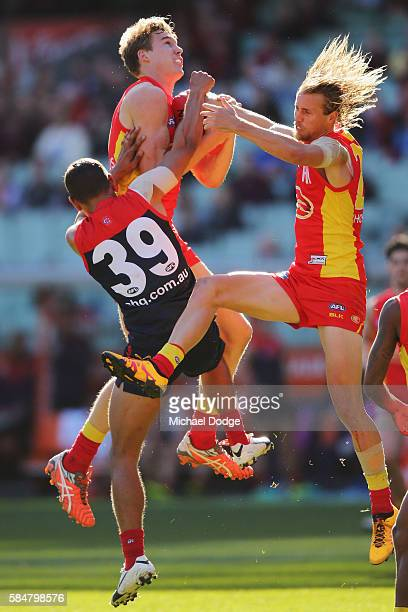 Tom Lynch of the Suns marks the ball next to teammate Matthew Shaw and against Neville Jetta of the Demons against during the round 19 AFL match...