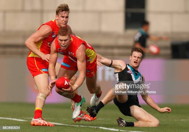 Tom Lynch of the Suns Peter Wright of the Suns and Tom Jonas of the Power in action during the 2017 AFL round 08 match between the Gold Coast Suns...