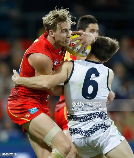 Tom Lynch of the Sunsis tackled by Lincoln McCarthy of the Cats during the 2018 AFL round 11 match between the Gold Coast Suns and the Geelong Cats...