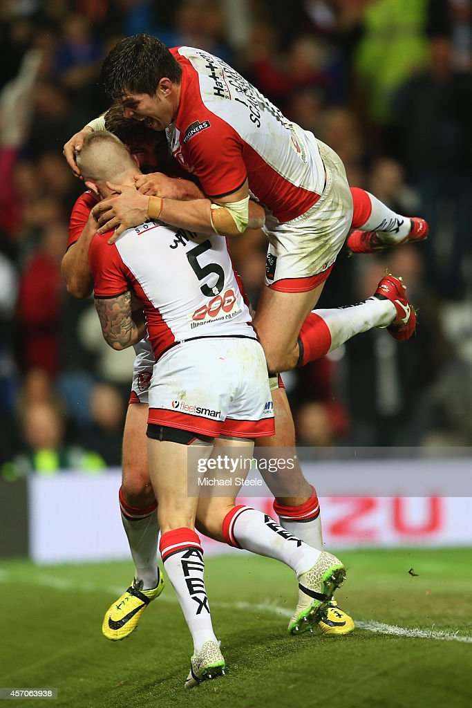 Tom Makinson of St Helens is smothered by Louie McCarthy-Scarsbrook (R) and Adam Swift (L) after scoring the crucial second try during the First Utility Super League Grand Final match between St Helens and Wigan Warriors at Old Trafford on October 11, 2014 in Manchester, England.
