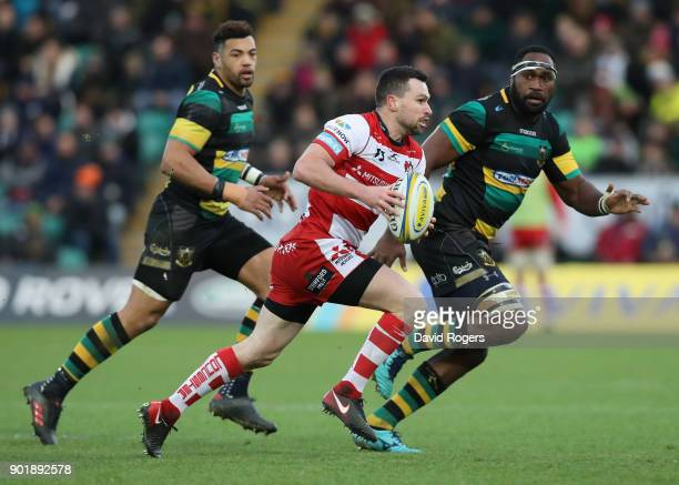 Tom Marshal of Gloucester runs with the ball watched by Api Ratuniyarawa and Luther Burrell during the Aviva Premiership match between Northampton...