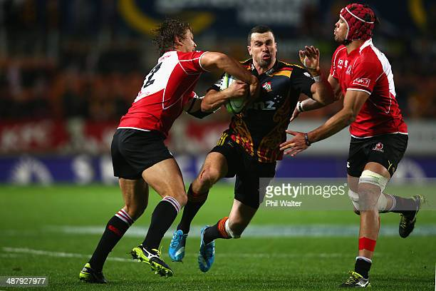 Tom Marshall of the Chiefs is tackled by Stefan Watermeyer and Warren Whiteley of the Lions during the round 12 Super Rugby match between the Chiefs...