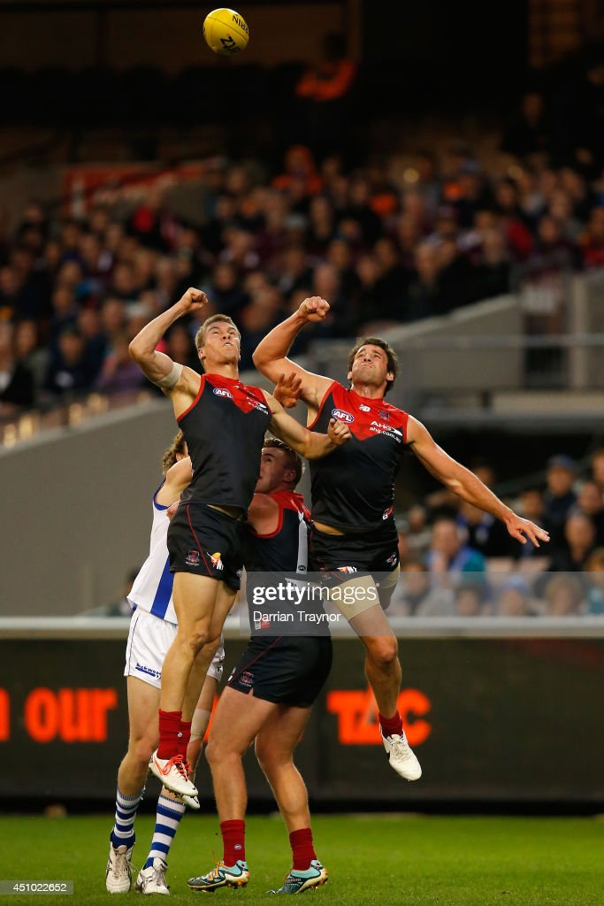 Tom McDonald and Cameron Pedersen of the Demons punch the ball during the round 14 AFL match between the Melbourne Demons and the North Melbourne Kangaroos at Melbourne Cricket Ground on June 22, 2014 in Melbourne, Australia.