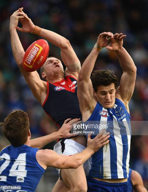 Tom McDonald of the Demons attempts to mark over the top of Scott Thompson of the Kangaroos during the round 19 AFL match between the North Melbourne...