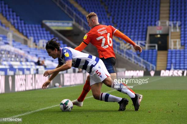 Tom McIntyre of Reading FC is challenged by James Bree of Luton Town during Carabao Cup Second Round match between Reading FC and Luton Town at...