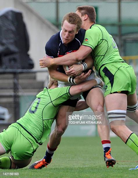 Tom McQueen of Hong Kong is tackled by Australia's Matt Lucas and Sean Mcmahon during the pool B match of the 2012 Tokyo Sevens World Series rugby...