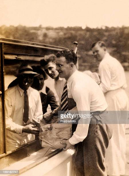 Tom Mitchell helping to load the boat as a goup of the MCC England cricket team prepare for an excursion near Sydney January 1933 The four identified...