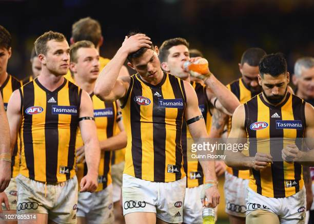Tom Mitchell Jaeger O'Meara and Paul Puopolo of the Hawks look dejected after losing the AFL First Qualifying Final match between the Richmond Tigers...