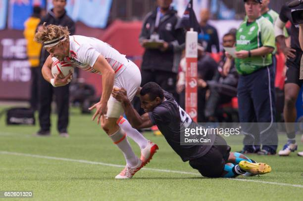 Tom Mitchell of England is dragged down by Jerry Tuwai of Fiji during day 2 of the 2017 Canada Sevens Rugby Tournament on March 12 2017 in Vancouver...