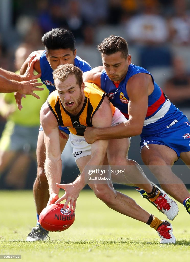 Tom Mitchell of the Hawks competes for the ball with Lin Jong of the Bulldogs and Luke Dahlhaus of the Bulldogs during the AFL JLT Community Series match between the Western Bulldogs and the Hawthorn Hawks at Mars Stadium on March 3, 2018 in Ballarat, Australia.