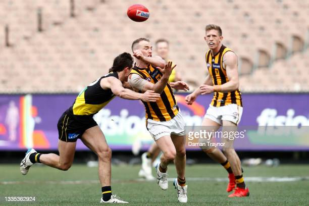 Tom Mitchell of the Hawks handballs during the round 23 AFL match between Richmond Tigers and Hawthorn Hawks at Melbourne Cricket Ground on August...