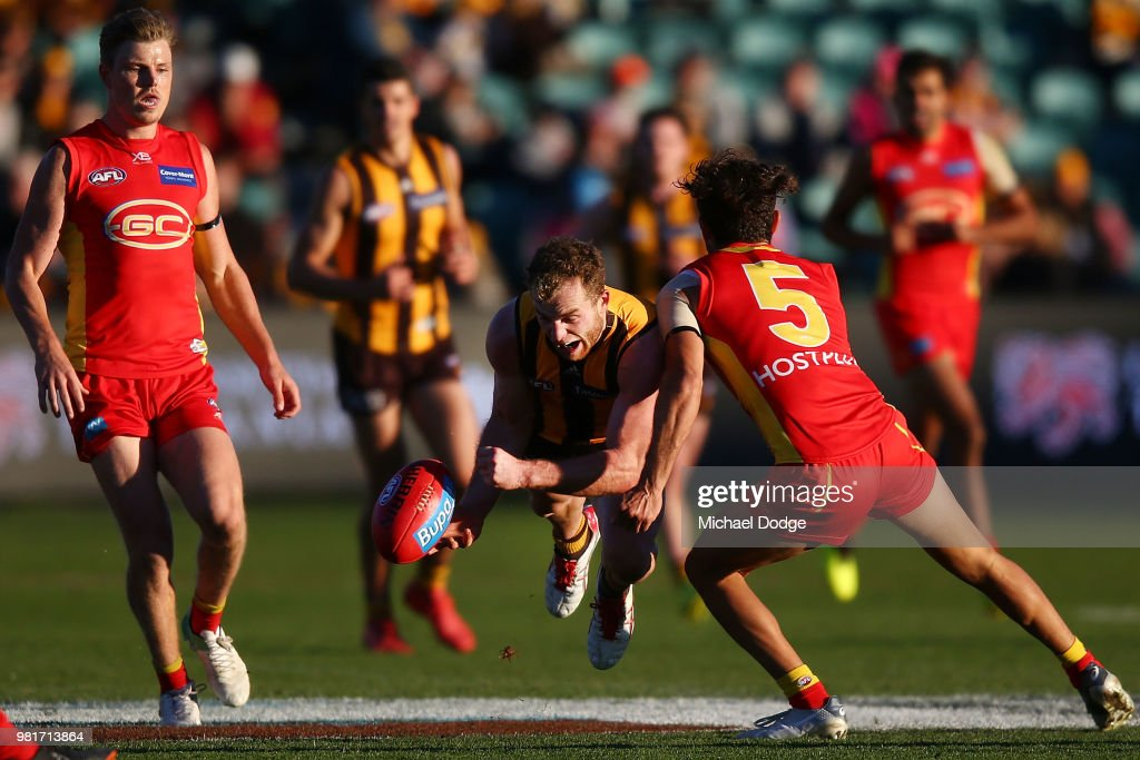 Tom Mitchell of the Hawks handballs from Jarrod Harbrow of the Suns during the round 14 AFL match between the Hawthorn Hawks and the Gold Coast Suns at University of Tasmania Stadium on June 23, 2018 in Launceston, Australia.