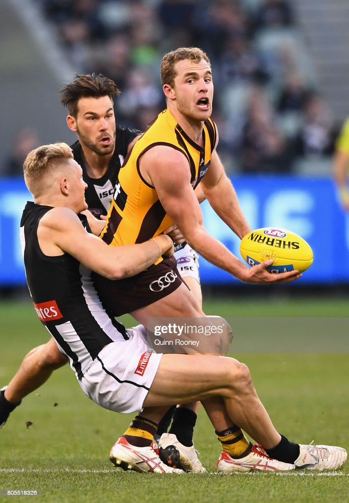 Tom Mitchell of the Hawks handballs whilst being tackled Adam Treloar of the Magpies during the round 15 AFL match between the Hawthorn Hawks and the Collingwood Magpies at Melbourne Cricket Ground on July 2, 2017 in Melbourne, Australia.