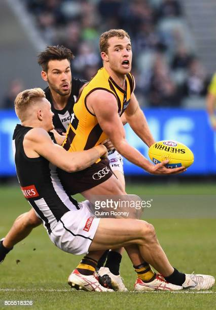 Tom Mitchell of the Hawks handballs whilst being tackled Adam Treloar of the Magpies during the round 15 AFL match between the Hawthorn Hawks and the...