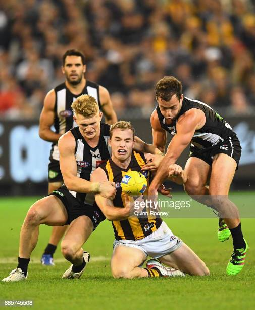 Tom Mitchell of the Hawks handballs whilst being tackled by Adam Treloar and Jarryd Blair of the Magpies during the round nine AFL match between the...