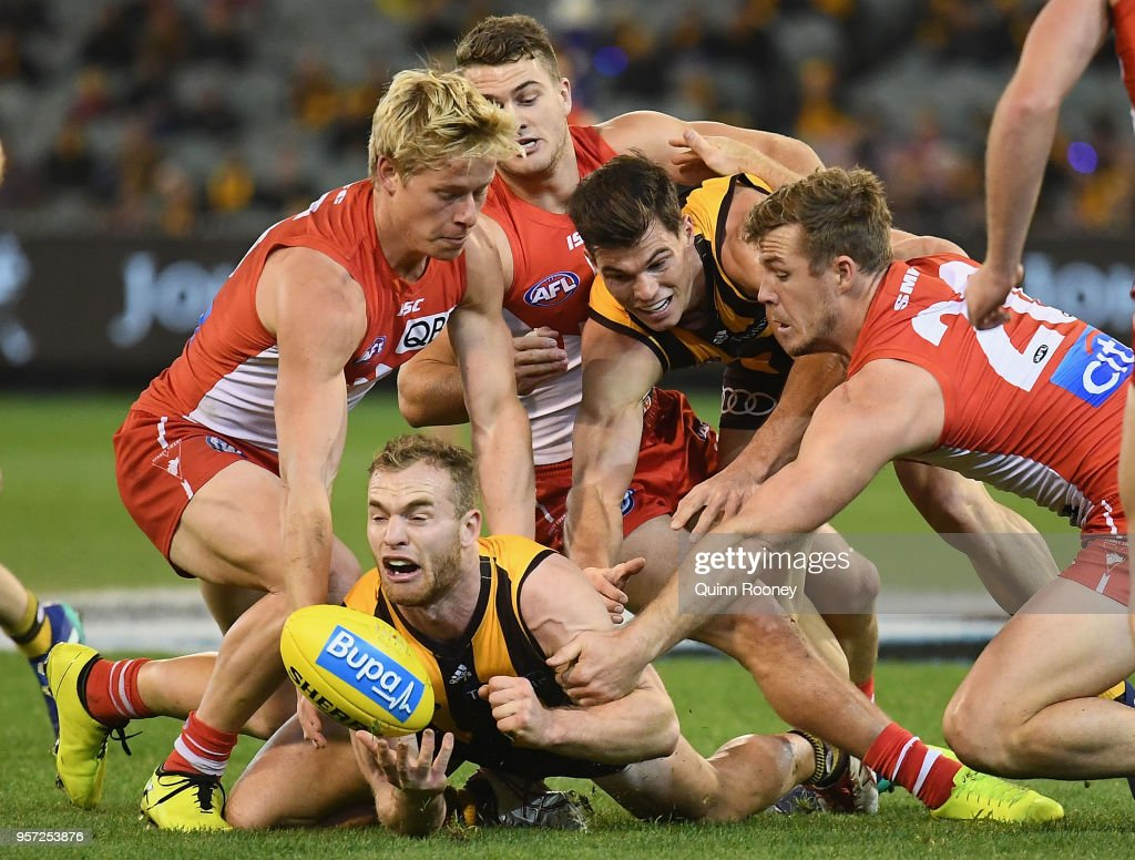 Tom Mitchell of the Hawks handballs whilst being tackled during the round eight AFL match between the Hawthorn Hawks and the Sydney Swans at Melbourne Cricket Ground on May 11, 2018 in Melbourne, Australia.