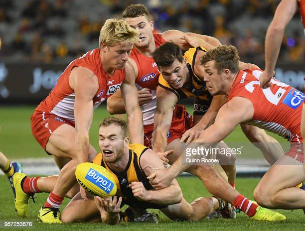 Tom Mitchell of the Hawks handballs whilst being tackled during the round eight AFL match between the Hawthorn Hawks and the Sydney Swans at...