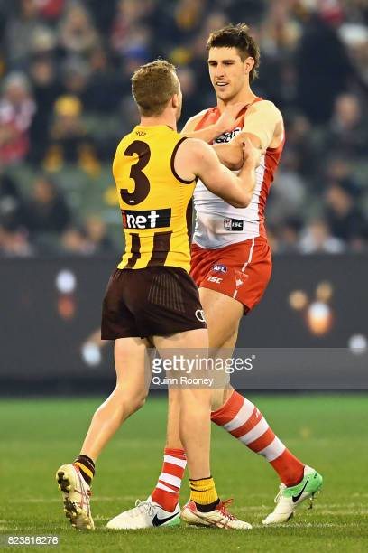 Tom Mitchell of the Hawks is pushed by Sam Naismith of the Swans during the round 19 AFL match between the Hawthorn Hawks and the Sydney Swans at...